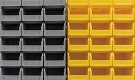Plastic gray and yellow containers are stacked in several rows royalty free stock images