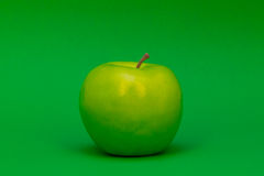 Apple on Green. A plastic green apple on a green background Stock Images