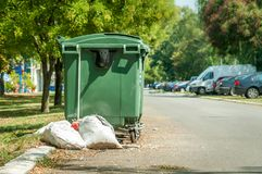 Plastic green garbage cans on the street in the city with junk bags full of litter on the asphalt road.  stock image