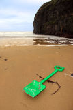 Plastic green spade on golden beach Royalty Free Stock Photo