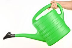 Plastic green watering can for plants in hand isolated on white. Plastic green watering can for plants in hand isolated on white stock photo