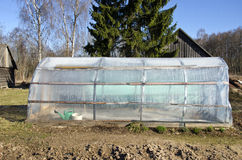 Plastic greenhouse in spring farm garden Royalty Free Stock Photo