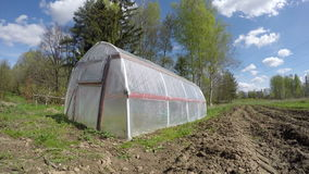 Plastic greenhouse in wind and clouds. Timelapse 4K stock video footage