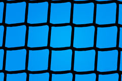 Plastic grid backlit against a blue background Royalty Free Stock Photos