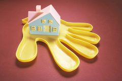 Plastic Hand Holding Toy House. With Red Background royalty free stock photography