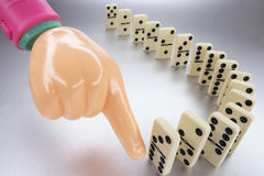 Plastic Hand and Row of Dominoes Royalty Free Stock Photography