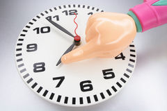 Plastic Hand and Wall Clock Stock Photos