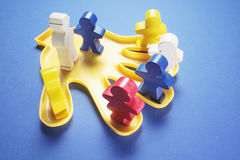 Plastic Hand with Wooden Figures Royalty Free Stock Photo