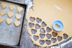 Plastic heart shaped cookie cutter and raw dough cookies on meta Royalty Free Stock Image