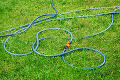 Plastic hose on green grass Royalty Free Stock Photos