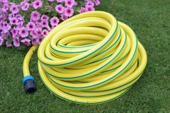 Plastic hose pipe. Yellow plastic hose pipe in a garden royalty free stock photo