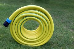 Plastic hose pipe. Yellow plastic hose pipe on a grass royalty free stock photo
