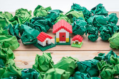 Plastic house building with trash paper balls Stock Image