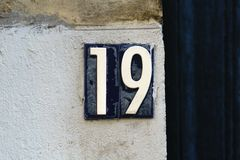 House number 19. Plastic house number nineteen 19on a plastered wall Stock Photo