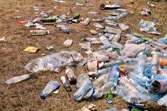 Plastic huisdierenflessen verlaten op gras na een partij, gebeurtenis Gebruikte lege die flessen weg ter plaatse na een openlucht Stock Afbeeldingen
