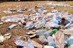 Plastic huisdierenflessen verlaten op gras na een partij, gebeurtenis Gebruikte lege die flessen weg ter plaatse na een openlucht Royalty-vrije Stock Afbeelding