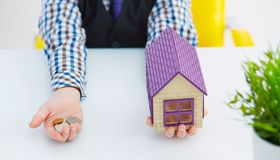Plastic huisstuk speelgoed en geld in weinig jongens` s handen Investeer in Onroerende goederen royalty-vrije stock afbeelding