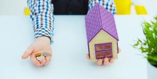 Plastic huisstuk speelgoed en geld in weinig jongens` s handen Investeer in Onroerende goederen stock foto
