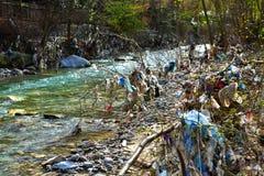 Plastic Huisvuilverontreiniging in bergstroom royalty-vrije stock fotografie