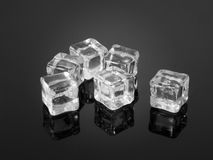 Plastic ice cubes reflected on textured surface. Stock Image