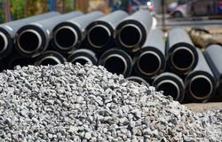 Plastic industrial drain pipe next to a pile of gravel. Royalty Free Stock Images