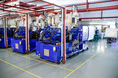 Plastic injection machines. Row of plastic injection machines at empty clean workshop royalty free stock photo
