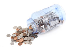 Plastic jar with coins. A plastic container with coins spilling out of it - saving money Stock Images
