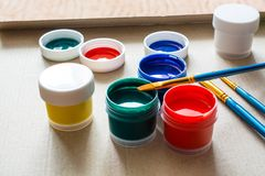 Plastic jar with green, yellow, blue and red acrylic paint and brush above. Royalty Free Stock Photos