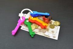 Plastic keys and money on gray background Stock Photo