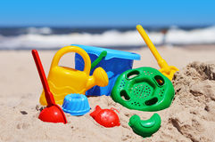 Plastic kinderenspeelgoed op het zandstrand Stock Fotografie