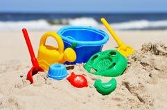 Plastic kinderenspeelgoed op het zandstrand Royalty-vrije Stock Afbeeldingen