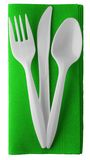 Plastic knife fork and spoon on napkin - isolated. Disposable plastic cutlery. On bright green paper napkin Royalty Free Stock Photo