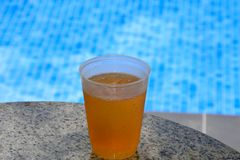 Plastic lager cup by the pool. Plastic lager cup of beer by the pool Stock Images