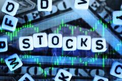 "Plastic letter cubes spelling ""stocks"" on us dollars bills background Stock Photo"