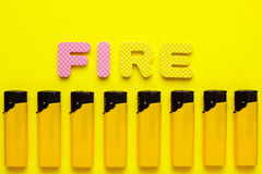 Plastic lighters and word fire on yellow background Royalty Free Stock Image