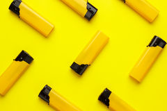 Plastic lighters on yellow background Royalty Free Stock Photography