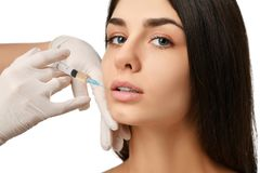 Plastic lips surgery beauty concept young brunette woman face and  doctor hand in glove with syringe Stock Photos