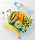 Plastic lunch box with sandwich, fruits, vegetables, nuts and water on white wooden table. Top view Royalty Free Stock Photo