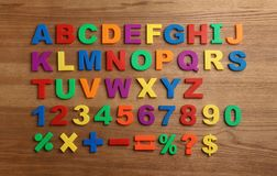 Plastic magnetic letters, numbers and math symbols on wooden background. Top view stock photo