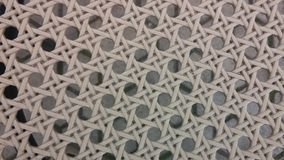 Plastic material netting texture. Texture of a synthetic chair material with circles and braiding look. Beneath this is the ground texture Royalty Free Stock Photo