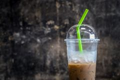 Plastic materials use, show transparent cup and green straw with partly consumed iced coffee inside.  stock photos