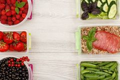 Plastic meal prep containers with black currant, strawberries, r. Aspberries, green peas, boiled buckwheat porridge and slices of meat, fresh cucumbers and salad Royalty Free Stock Photography