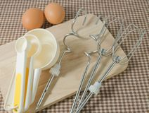 Plastic Measuring Spoons with Metal Whisk and Egg Royalty Free Stock Photos
