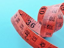 Plastic measuring tape blue background stock photography