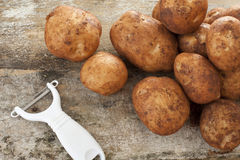 Plastic and metal peeler with raw potatoes Royalty Free Stock Photography