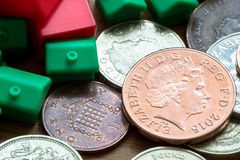 Plastic Model Houses and English Coins. Imitation model red and green plastic houses with chimneys rest on top of British coins of differing values and colors Royalty Free Stock Photo
