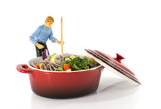 Man stirring vegetarian food in red saucepan Stock Images