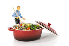 Man stirring vegetarian food in red saucepan Royalty Free Stock Photography