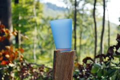 Plastic mug in the nature on a tree trunk in a wooded landscape background stock image