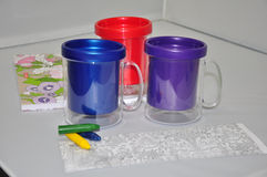 Plastic mugs and crayons. Three colorful mugs, red, blue and purple on a table with green yellow and blue crayons lying alongside Royalty Free Stock Images